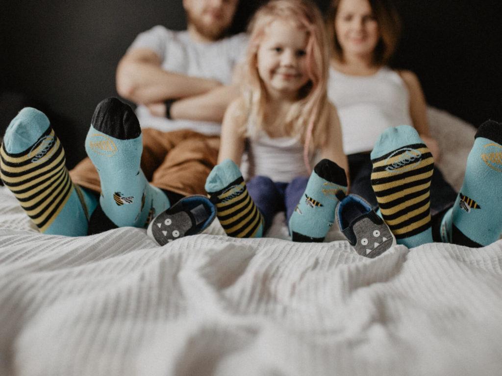 dziewczynka z rodzicami w kolorowych skarpetkach na łózku guzikfotografuje