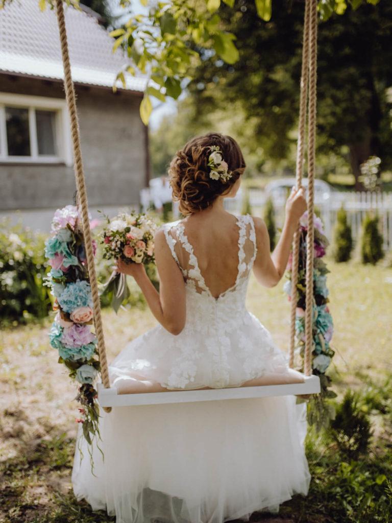 kobieta w sukni ślubnej na huśtawce guzikfotografuje