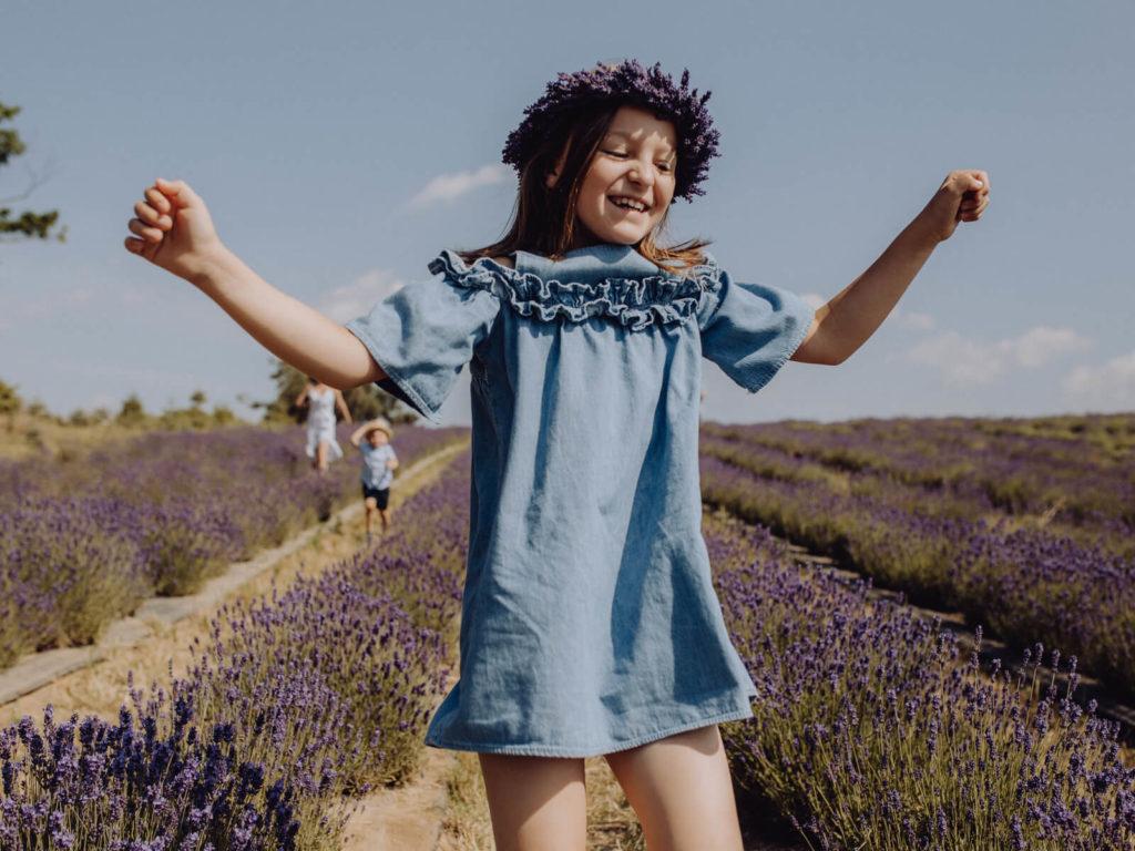 radosna dziewczynka skacząca na polu portfolio guzikfotografuje