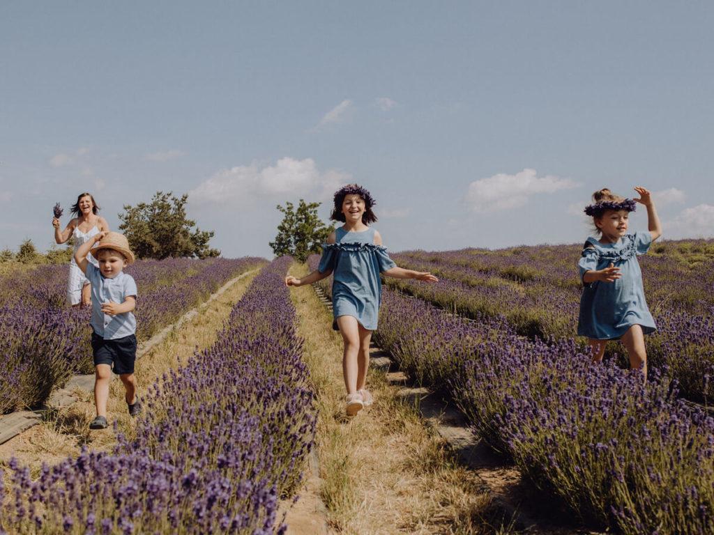 biegnące dzieci z wiankami na polu wraz z mamą portfolio guzikfotografuje