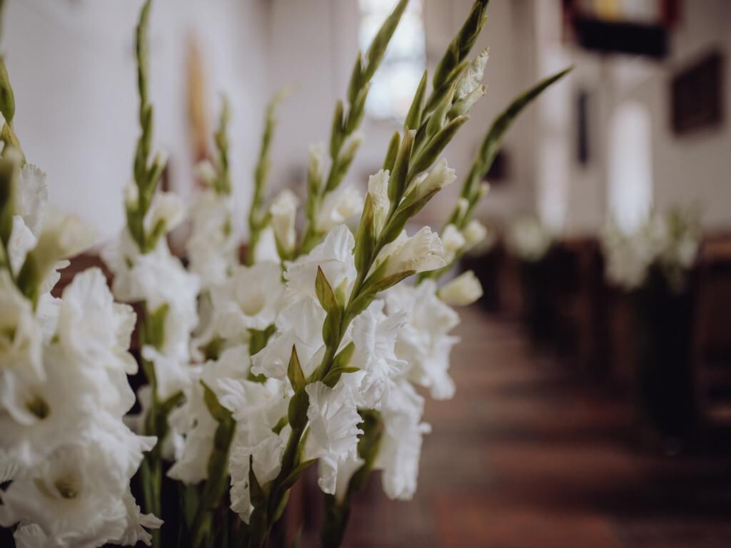 białe kwiaty w kościele na ślubie guzikfotografuje