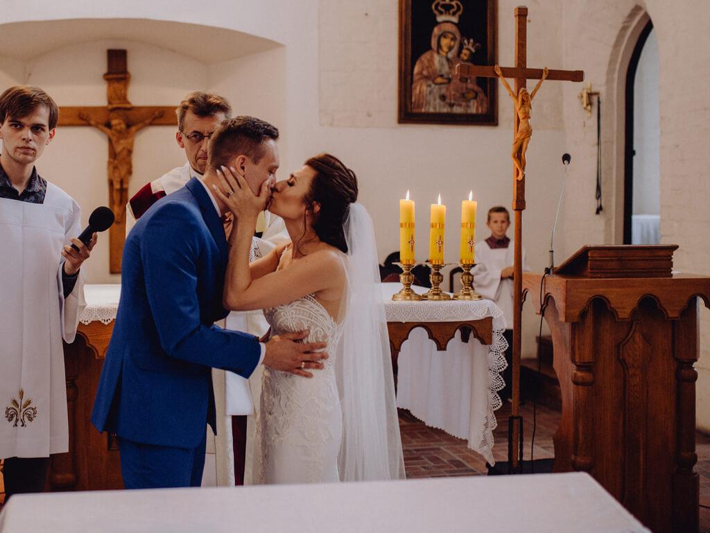 pocałunek pary młodej przed ołtarzem guzikfotografuje