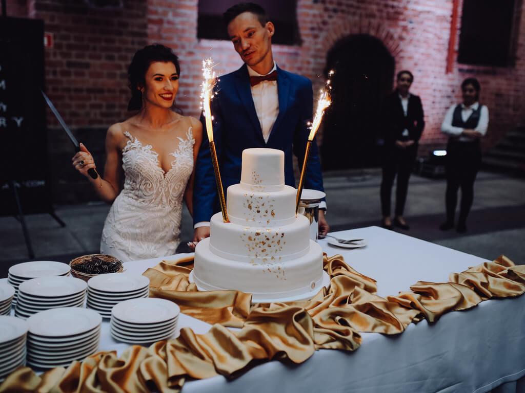 para młoda krojąca tort na weselu guzikfotografuje